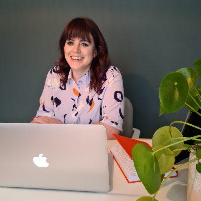 Emma Abbey headshot with laptop