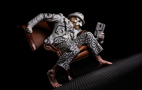 The Riddle. A dancer in a white suit on a leather chair